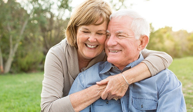 Older man and woman smiling after all on 4 tooth replacement