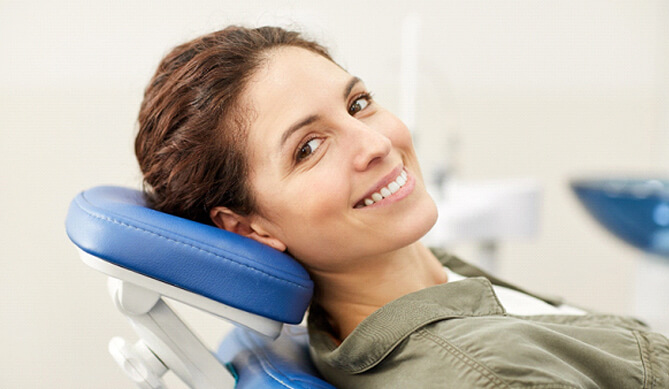 Female patient leaning back in chair and smiling