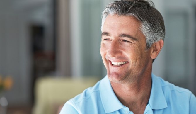 Man with flawless smile after dental implant tooth replacement