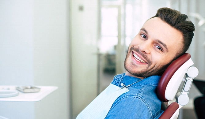 Man smiling in a dental chair with denim jacket