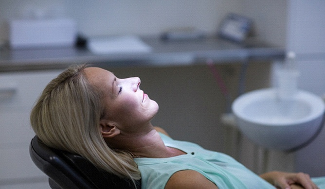 Woman sitting in dental chair with her eyes closed