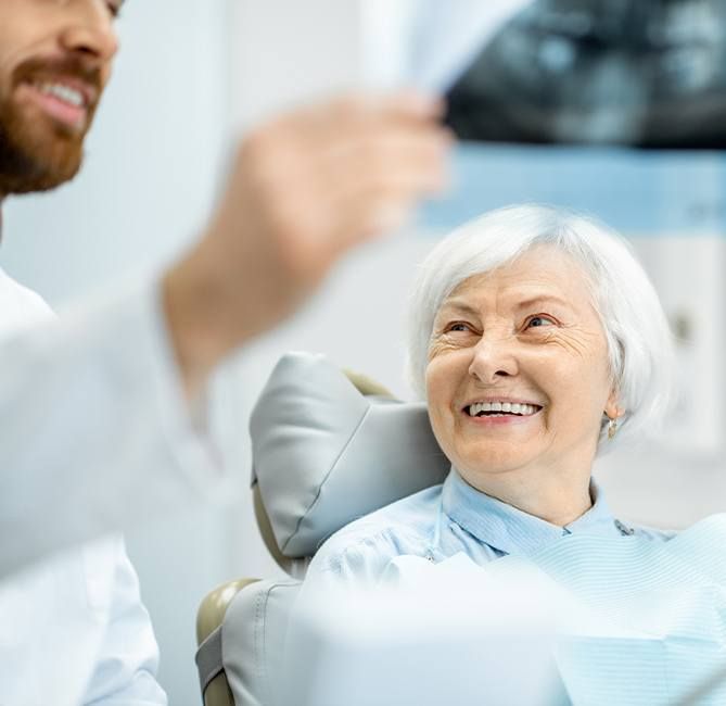 Older female patient talking to periodontist